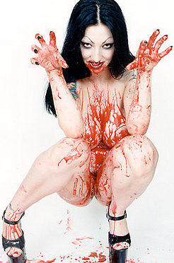 Tattooed vampire girl covers herself in blood