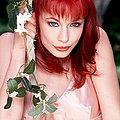 innocent redhead in pink slip on outdoor swing