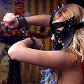 Slave girl in leather costume and leather mask spreading her legs